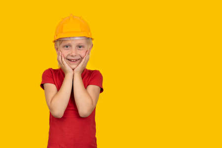 Joyful blond boy in hard hat on yellow background. Choice of specialty.