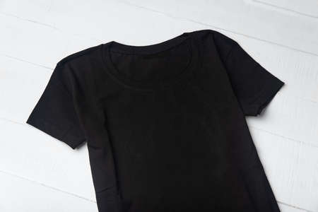 Black knitted t-shirt without pattern on white background. Mockup. Close up