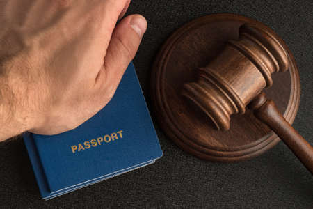 Male hand holds passport next to wooden gavel. Obtain citizenship. Legal immigration