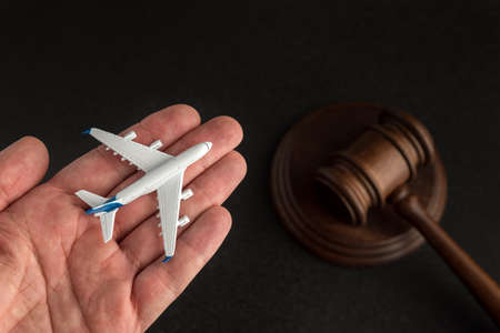 Airplane model in hand on background of wooden Judges gavel. Claim to airline