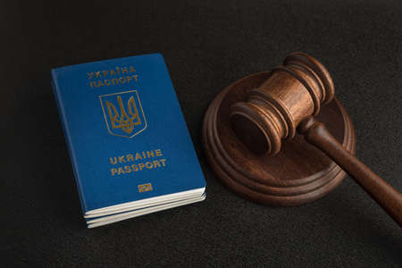 Passport of a citizen of Ukraine and a judicial hammer on a black background. Legal immigration. Obtain citizenship