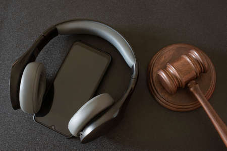 Judges gavel smartphone and headphones on black background. Top view. Music auction.
