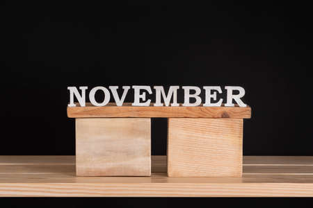 Word November by wooden letters on black background. Front view. Autumn calendar. Fall month