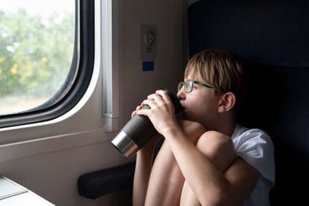 Child in compartment carriage is drinking tea and looking out the window. Travel by railway
