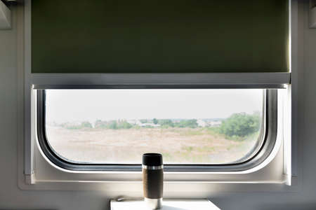 Window in train carriage. Thermo mug is on table against the background of window in train. Rail travel. 免版税图像