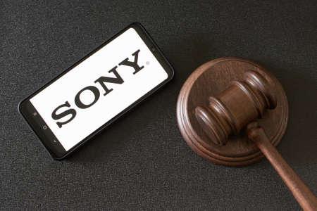 KHARKOV, UKRAINE - JUNE 25, 2020: Smartphone with Sony logo on screen next to the judges gavel Editöryel