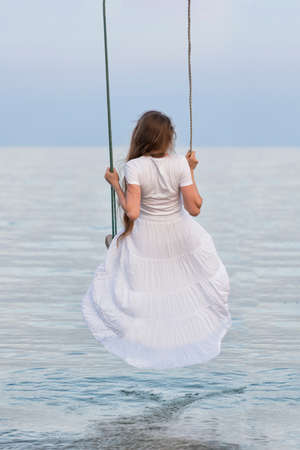 Beautiful young woman sits on rope swing on sea background. Vertical frame. Back view.