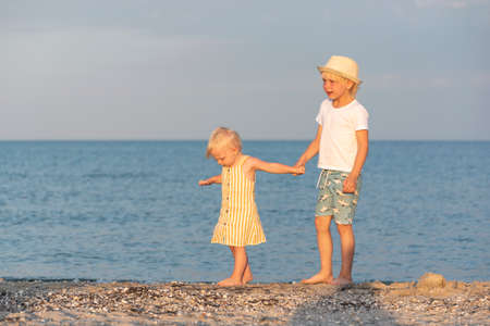 Brother holds his little sister by hand and walks barefoot along the beach