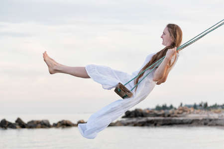 Beautiful woman in white dress rides a rope swing over water. Vacantion at the sea Stock Photo