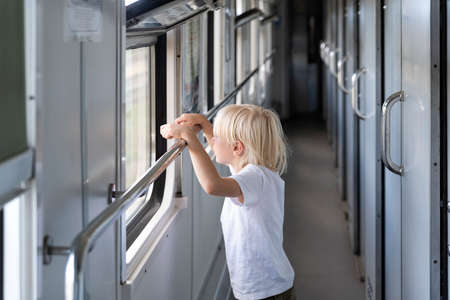 Blond boy in railway carriage. Handsome kid looking out of train window.