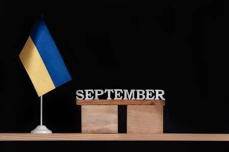 Wooden calendar of September with Ukrainian flag on black background. Dates in Ukraine in September Archivio Fotografico