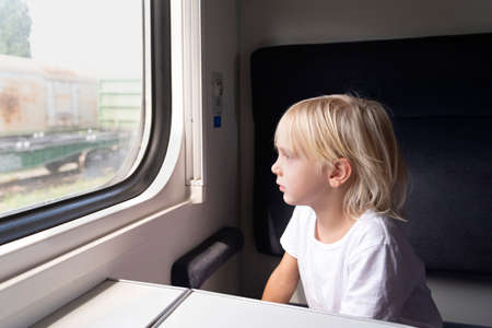 Little blond boy looks thoughtfully out the train window. Rail travel with children.