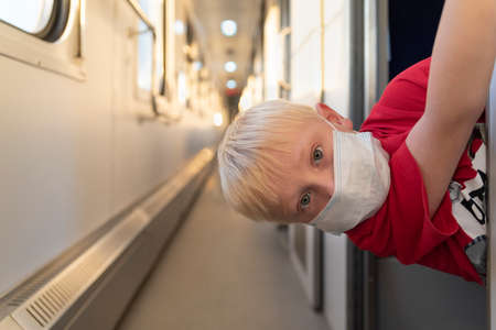 fair-haired boy in protective mask on train compartment. Train travel rules during pandemic and quarantine.
