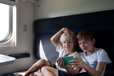 Two brothers in compartment carriage gaming at smartphone. Entertaining children during trip. Travel by railway