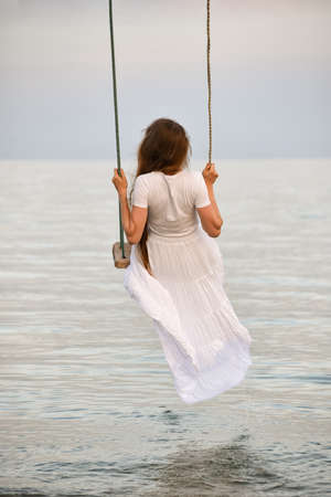 Girl in white dress sits on swing above the water. Romance. Vertical frame. Back view.