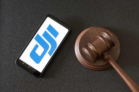 KHARKOV, UKRAINE - JUNE 25, 2020: Dji logo on the phone display and judges gavel on black background. Top view Editöryel