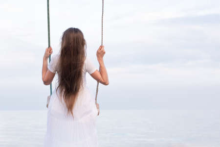 Portrait of girl. Back view. Young woman in white dress with loose hair sits on rope swing on sea backdrop. Archivio Fotografico