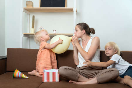 Mom and two children are preparing for the holiday. Mom inflates the balloon. Banco de Imagens