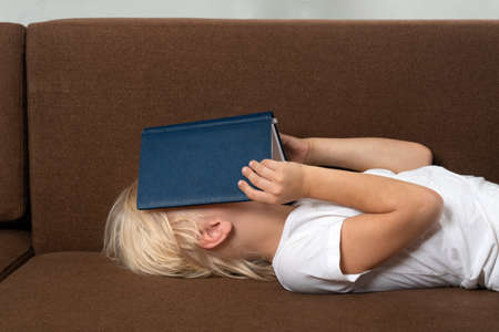 Child on couch putting book on his face. Covering face with book