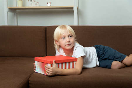 Child lies on the couch with gift box in his hands. Blond boy holding bright box in his hands. Stok Fotoğraf