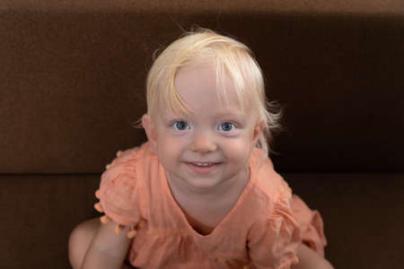 Portrait of little blonde girl. Blonde girl looking at camera and smiling.
