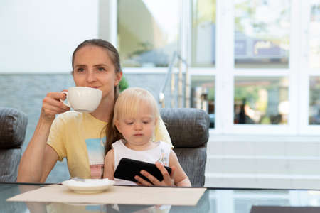 Happy young mom drinks coffee and holds child in her arms. Kid watching cartoons on phone while mom is relax.