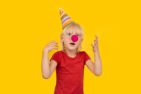 Surprised boy in clown outfit on yellow background. Childrens holiday. Stok Fotoğraf