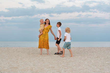 Happy family on beach. Family lifestyle. Mom and three children having fun on the sea. 免版税图像