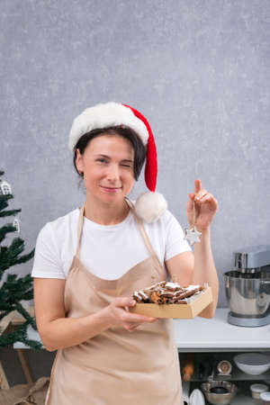 Confectioner woman in New Years hat and kitchen robe holds box of delicious sweets and winks. Vertical frame. Stock Photo