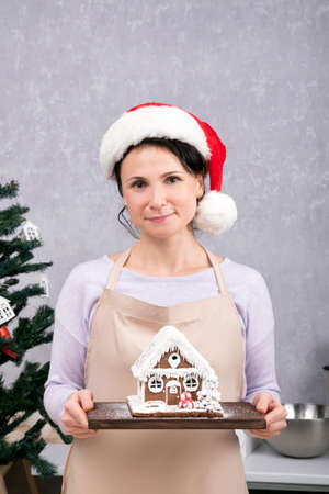 Pretty woman chef in Santa hat holds gingerbread house in her hands. Vertical frame.