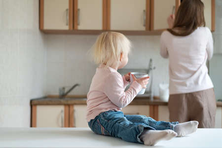 Mom and two-year-old baby with cup in their hands in kitchen
