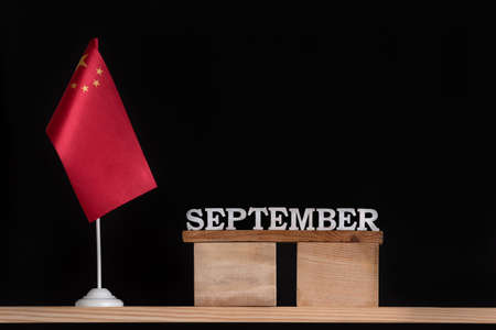 Wooden calendar of September with Chinese flag on black background. Holidays of China in September