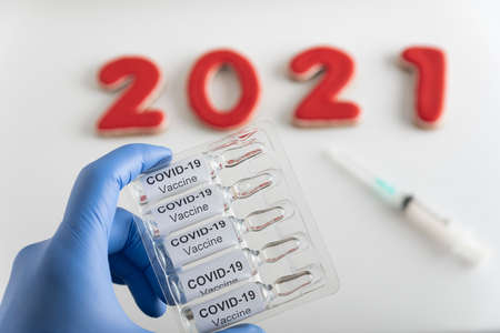 Hand in medical gloves holds ampoules with COVID-19 label against inscription 2021 background. Coronavirus vaccine.