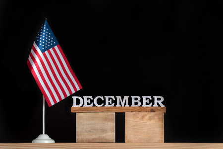 Wooden calendar of December with USA flag on black background. Holidays of the United States of America in winter