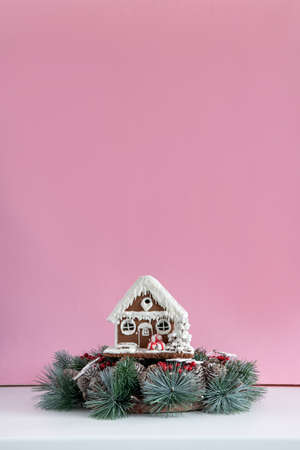 Christmas wreath and gingerbread house on pink background. New Years and Christmas. Copy space.
