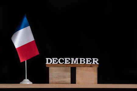 Wooden calendar of December with French flag on black background. Holidays of France in December Stok Fotoğraf
