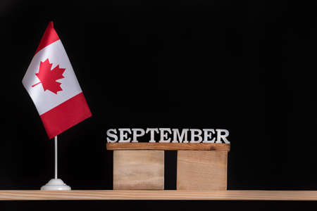 Wooden calendar of September with Canadian flag on black background. Autumn holidays in Canada. Stok Fotoğraf