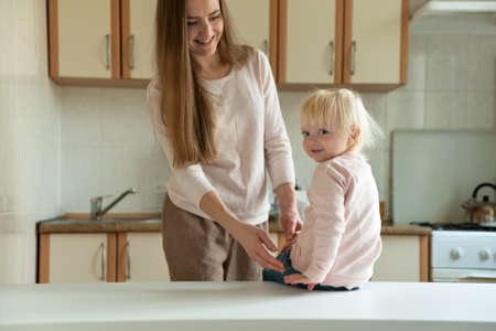 Young happy mom and blonde baby in the morning in kitchen. Family breakfast. Stok Fotoğraf