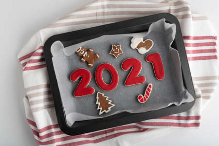 Set of numbers 2021 from ginger biscuits glazed sugar icing on baking sheet.