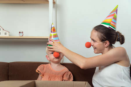 Mom and baby are preparing for holiday. Mom puts on party hat and clown nose for her little daughter.