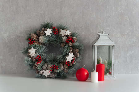 Christmas decorations: christmas wreath, lantern and candles on gray background. Cozy interior.