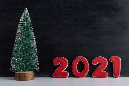 Artificial Christmas tree and red numbers 2021 on black background. New year concept. Copy space. Stok Fotoğraf