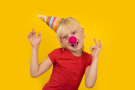 Happy blond boy celebrating his birthday. Child in party hat, red clown nose on yellow background
