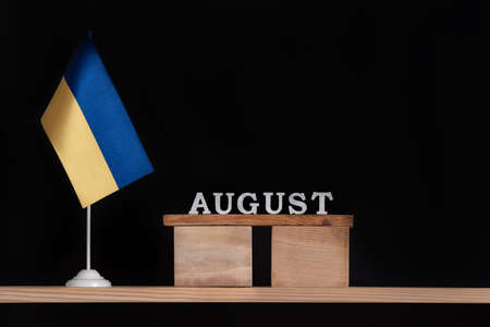 Wooden calendar of August with Ukrainian flag on black background. Dates in Ukraine in August.