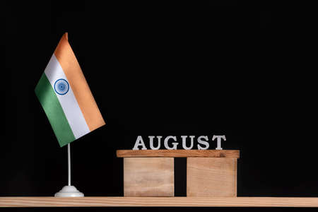 Wooden calendar of August with Indian flag on black background. Holidays of India in August