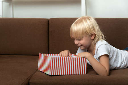 Child opens the gift box and looks into it