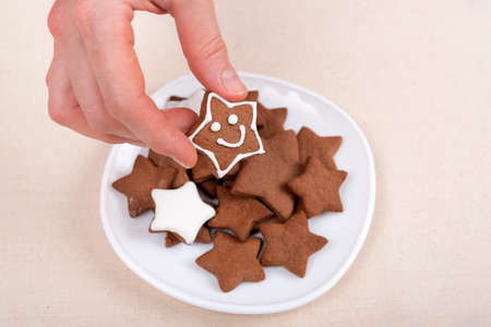 Female hand holds a gingerbread cookie in shape of star emoticon. glazed painted cookies.