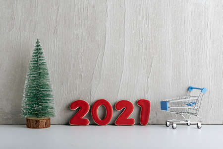 Small Christmas tree, shopping cart and numbers 2021 on light background. Shopping before the new year. Stok Fotoğraf