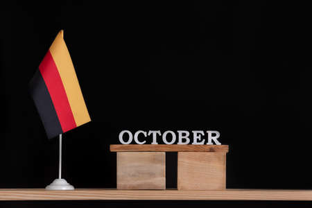 Wooden calendar of October with German flag on black background. Dates in Germany in October Stok Fotoğraf
