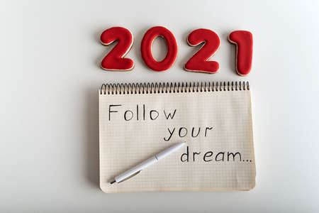 Top view numbers 2021 and notebook with words: FOLLOW YOUR DREAM. Wishlist for 2021.